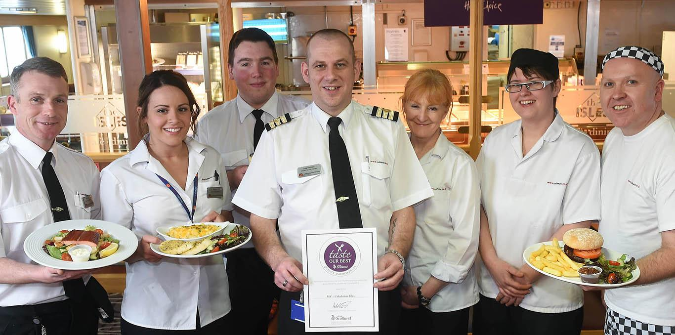 Taste our best award being held up by a group of CalMac ferries onboard catering staff.