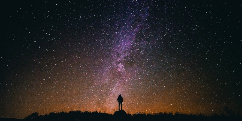 Person standing under the stars and milky way
