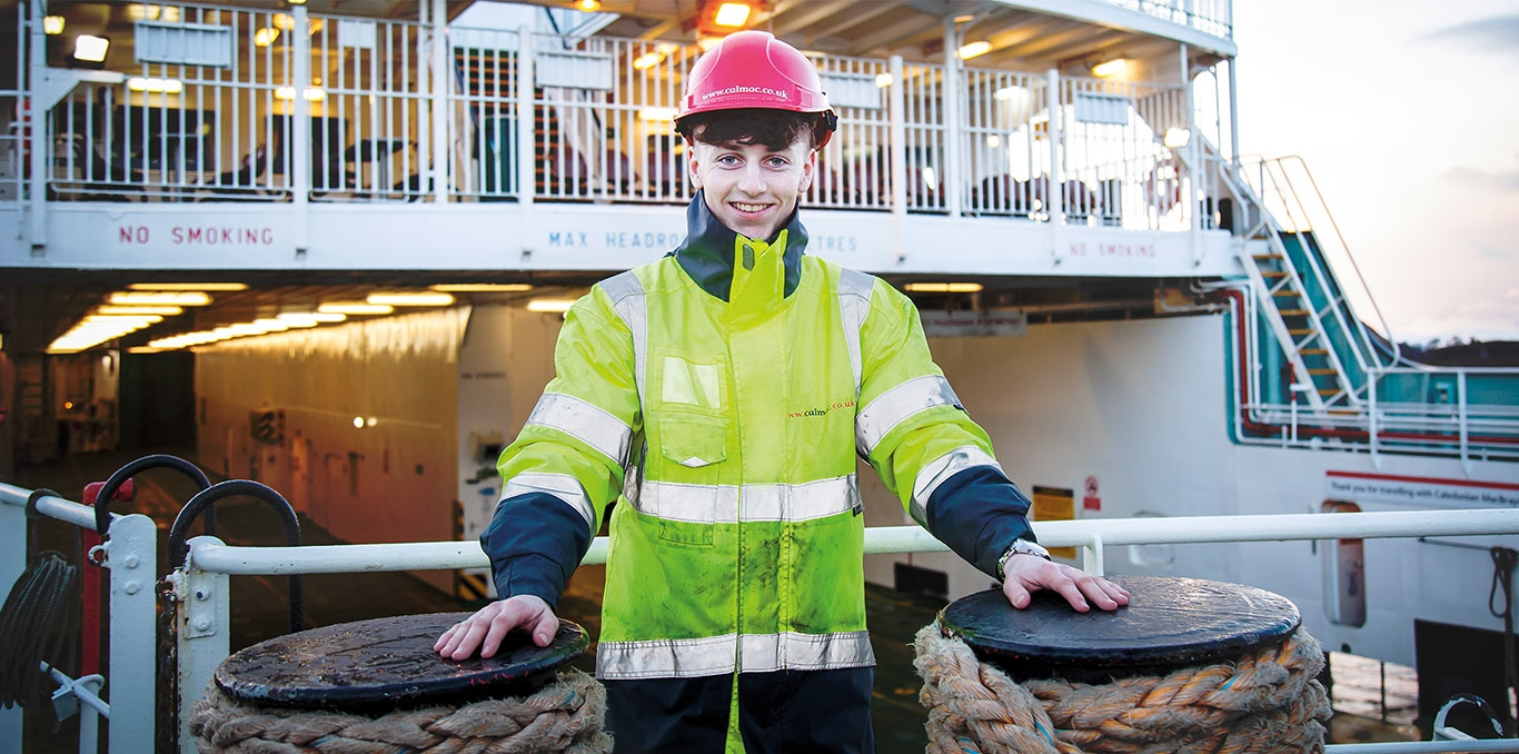 Young man with high vis standing on a ferry
