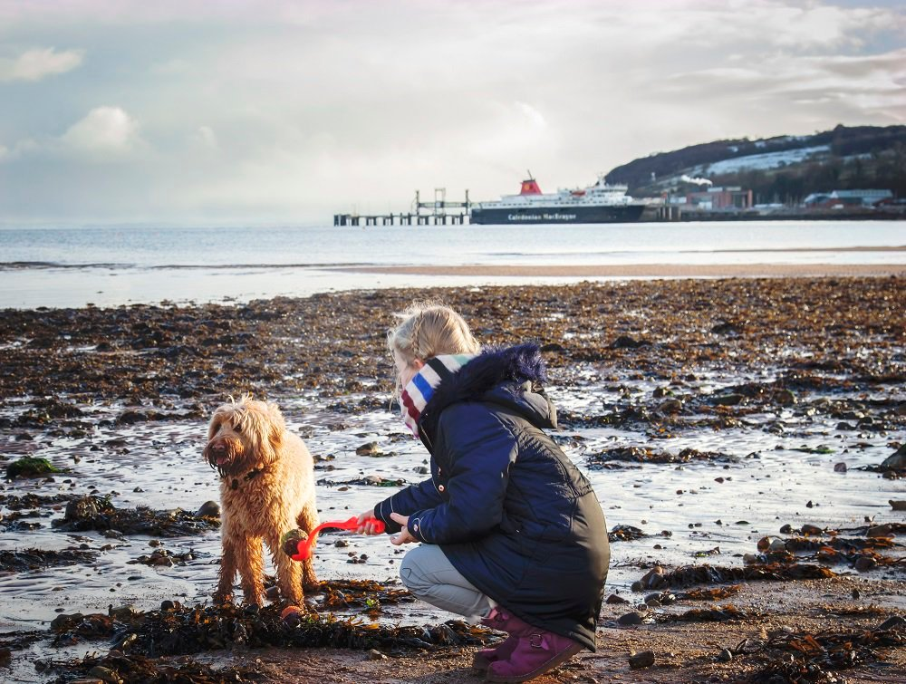 girl with dog on beach in Arran